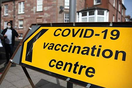 Hinter einem Schild eines Corona-Impfzentrums in Blairgowrie stehen zwei Menschen mit Mund-Nasen-Schutz. Foto: Andrew Milligan/PA Wire/dpa