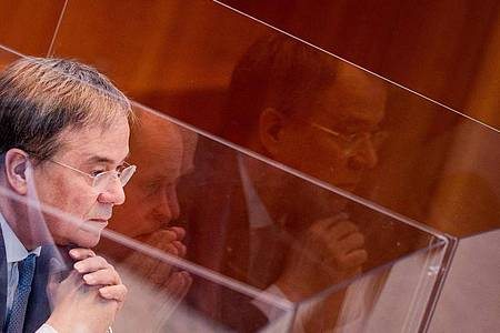 Armin Laschet sitzt in einer Box aus Plexiglas im Plenum des Landtags. Foto: Rolf Vennenbernd/dpa