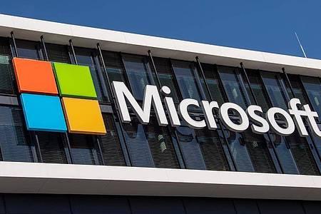 Das Microsoft Logo hängt an der Fassade eines Bürogebäudes in der Parkstadt Schwabing in München. Foto: Peter Kneffel/dpa