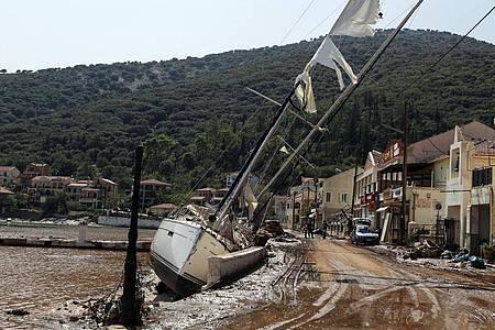 Eine Segelyacht liegt nach einem Sturm neben einer Straße in Kefalonia. Der Wirbelsturm «Ianos» im Westen und ein weiteres Sturmtief über der Nordägäis hatten am Freitag und Samstag in weiten Teilen Griechenlands schwere Schäden verursacht. Foto: Nikiforos Stamenis/AP/dpa