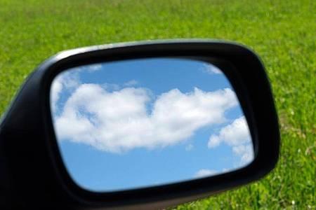 Blauer Himmel und Wolken im Außenspiegel eines Autos. Foto: Sebastian Willnow/dpa-Zentralbild/dpa