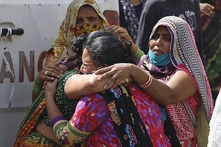 Frauen trauern in Ahmedabad um einen an Covid-19 gestorbenen Angehörigen. Foto: Ajit Solanki/AP/dpa