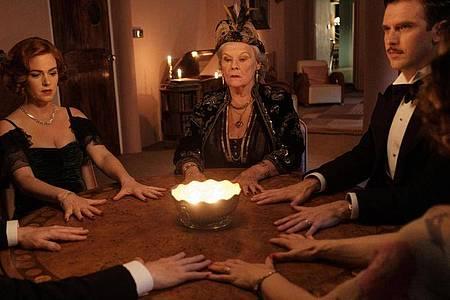 Geisterbeschwörung:Ruth Condomine (Isla Fisher l-r), Madame Arcati (Judi Dench) und Charles Condomine (Dan Stevens)bei einer Séance. Foto: Angus Young/Kochfilms/dpa