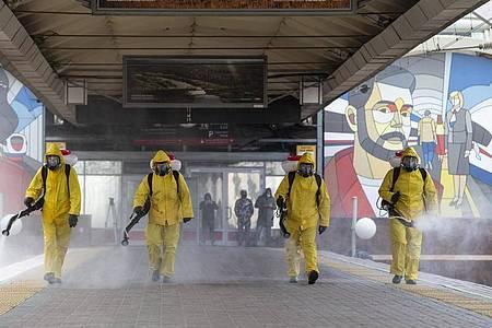 Städtische Angestellte desinfizieren einen Bahnhof in Moskau. Foto: Alexander Zemlianichenko Jr/XinHua/dpa