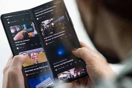 Online-Nachrichten wie in einem Buch lesen? Geht, wenn man das Display des Galaxy Z Fold 3 nicht komplett aufklappt. Foto: Franziska Gabbert/dpa-tmn