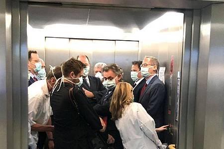 Bei einem Besuch der Uniklinik Gießen drängen sich Bundesgesundheitsminister Spahn (CDU, l), und Hessens Ministerpräsident Bouffier (CDU, M) mit Begleitern im Fahrstuhl. Foto: Bodo Weissenborn/Hessischer Rundfunk/dpa