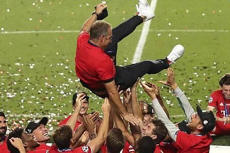 Ausgelassene Freude:Bayerns Cheftrainer Hansi Flick wird von seinen Spielern in die Luft geworfen. Foto: Miguel A. Lopes/Pool EPA/AP/dpa