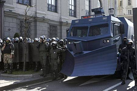 Bereitschaftspolizisten blockieren eine Straße mit einem Militärfahrzeug in Minsk. Foto: ---/AP/dpa