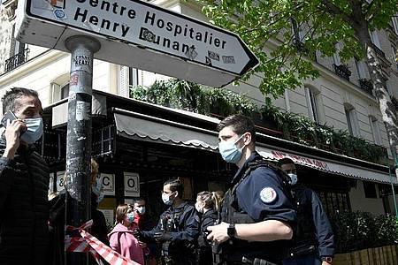 Polizisten sperren das Gebiet um das Krankenhaus Henry Dunant ab. In Paris ist mindestens ein Mensch in der Nähe eines Krankenhauses durch Schüsse getötet worden. Foto: Anne-Christine Poujoulat/AFP/dpa