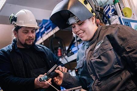 Schweißen gehört zu den Schwerpunkten in der Ausbildung zur Anlagenmechanikerin. Nico Wittlief, Ausbilder bei der BTB, erklärt Lisa-Maria Schippl den Umgang mit einem Elektroschweißgerät. Foto: Zacharie Scheurer/dpa-tmn