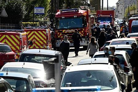 Polizisten und Feuerwehrleute stehen in der Nähe der Polizeistation in Rambouillet. Foto: Bertrand Guay/AFP/dpa