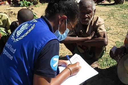 Eine Mitarbeiterin des Welternährungsprogramms spricht mit einigen Ältesten einer Gemeinde auf Madagaskar über ihre Situation. Foto: Fenoarisoa Ralaiharinony/Welternährungsprogramm WFP/dpa
