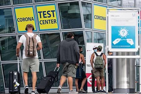 Ankommende Fluggäste gehen zu einem Corona- Testcenter am Flughafen München. Foto: Matthias Balk/dpa