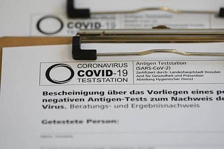 Anmeldebögen in einer Corona-Teststation in einem Cafè in der Dresdner Neustadt. Foto: Robert Michael/dpa-Zentralbild/ZB