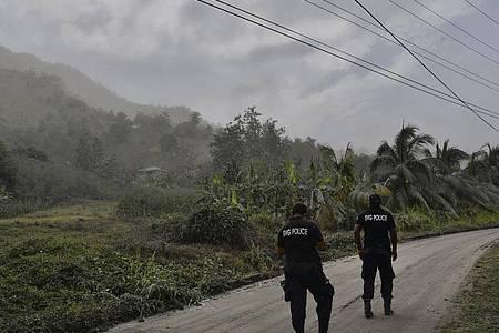 Polizisten patrouillieren auf einer aschebedeckten Straße auf der Karibikinsel St. Vincent, um Menschen davon abzuhalten, sich dem aktiven Vulkan La Soufrière zu nähern. Foto: Orvil Samuel/AP/dpa
