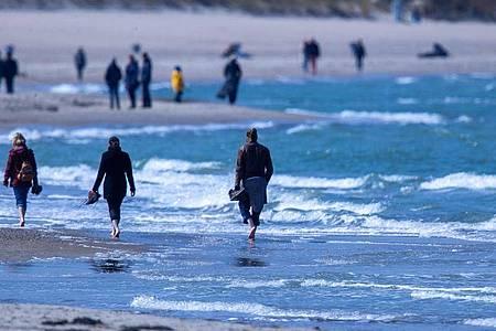 Spaziergänger am Strand von WArnemnünde. Foto: Jens Büttner/dpa-Zentralbild/dpa