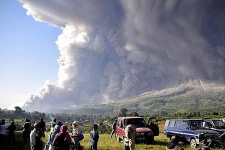 Menschen beobachten eine Eruption des Vulkans Sinabung. Foto: Uncredited/AP/dpa