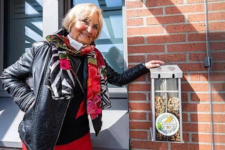 """Karin Meixner-Nentwig von dem Verein """"Amberger Kippenjäger"""" neben einem Sammelbehälter mit Zigarettenkippen. Foto: Armin Weigel/dpa"""