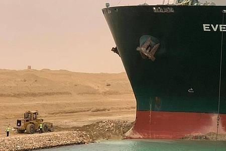 Ein Bagger versucht, das vordere Ende Containerschiffs Ever Given zu befreien, nachdem es im südlichen Ende des Suezkanals auf Grund gelaufen war. Foto: -/Suez Canal Authority via Egyptian Cabinet Facebook Page/dpa