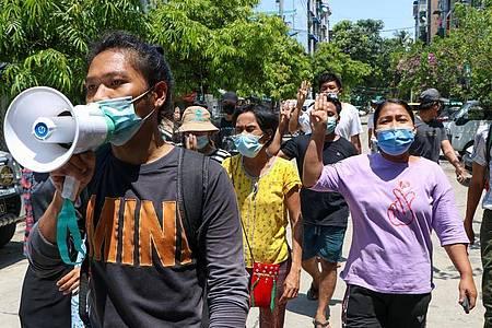 Menschen zeigen bei einer Demonstration in Yangon den Drei-Finger-Gruß als Zeichen des Widerstands. Foto: --/AP/dpa