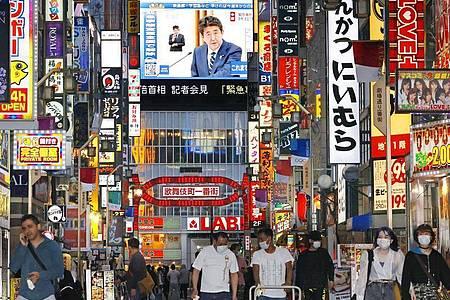 Eine große Leinwand in Tokio zeigt den japanischen Premierminister Shinzo Abe, der das Ende des Ausnahmezustands verkündet. Foto: -/kyodo/dpa