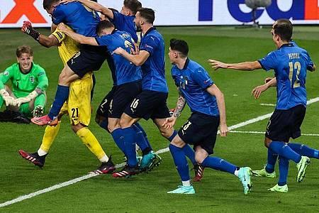 Italiens Spieler jubeln nach dem gewonnen Elfmeterschießen mit ihrem Torhüter Gianluigi Donnarumma. Foto: Christian Charisius/dpa