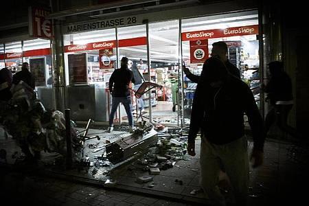 Menschen stehen in der Krawallnacht vor einem geplünderten Geschäft in der Stuttgarter Innenstadt. Foto: Julian Rettig/dpa