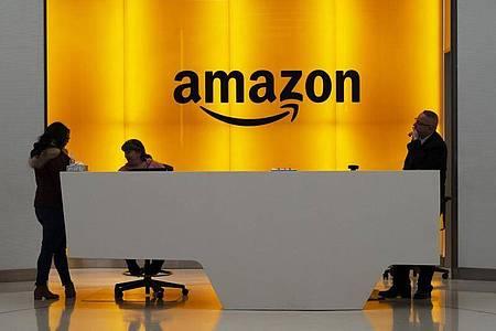 Menschen stehen in der Lobby der New Yorker Amazonas-Büros. Foto: Mark Lennihan/AP/dpa