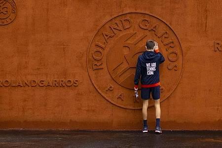Ein Balljunge berührt das Logo vom Stade Roland Garros. Foto: Peter Dejong/AP/dpa