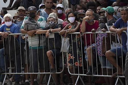 Menschen warten in einer Schlange inmitten der Corona-Pandemie auf eine von der Stiftung Leao XIII gespendete Mahlzeit. Foto: Silvia Izquierdo/AP/dpa