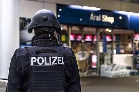 Ein Polizist sichert am frühen Morgen den Tatort. Foto: Christian Schulz/Foto Hosser/dpa