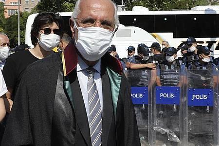 Mehmet Durakoglu, Vorsitzender der Anwaltskammer von Istanbul, geht an einer Barrikade aus Sicherheitskräften vorbei, die demonstrierenden Anwälten den Zugang zum Parlamentsgebäude am zweiten Tag in Folge versperren. Foto: Burhan Ozbilici/AP/dpa