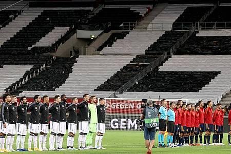 Die beiden Teams lauschen vor Spielbeginn vor leeren Rängen in Stuttgart den Nationalhymnen. Foto: Christian Charisius/dpa