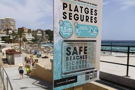 Ein Schild am Eingang zum Strand von Cala Major weist auf die Sicherheitsmaßnahmen hin, die die Verbreitung des Coronavirus verhindern sollen. Foto: Clara Margais/dpa