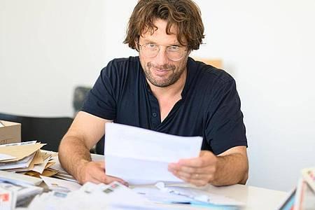 Friedrich von Borries, Initiator des Stipendiums für das Nichtstun, schaut in seinem Büro Bewerbungen für das Stipendium durch. Foto: Daniel Reinhardt/dpa