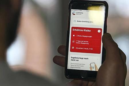 Auf einem Handy zeigt die «Corona Warn-App» ein erhöhtes Risiko an, welches darauf hinweist Kontakt mit einer infizierten Person gehabt zu haben. Foto: Kira Hofmann/dpa-Zentralbild/dpa