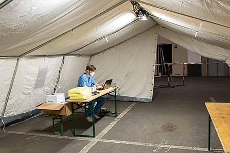 Ein medizinischer Helfer in einem aufgebauten Zelt für die Covid-19-Testung in der Tiefgarage des Iduna-Zentrum. Foto: Swen Pförtner/dpa