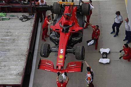 Die Boxenmannschaft von der Scuderia Ferrari überprüft am Ende des Trainings den Wagen von Sebastian Vettel. Foto: Frank Augstein/PoolAP/dpa