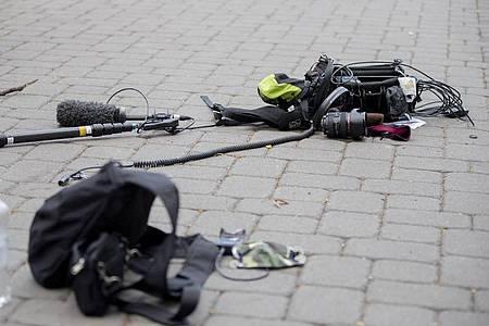 Die Ausrüstung eines Kamerateams liegt nach einem Überfall auf ein ZDF-Teams zwischen Alexanderplatz und Hackescher Markt auf dem Boden. Foto: Christoph Soeder/dpa
