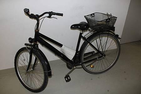 schwarzes Damenfahrrad mit einem Fahrradkorb, der auf dem Gepäckträger montiert ist, am Hinterrad befindet sich ein oranger Speichenreflektor
