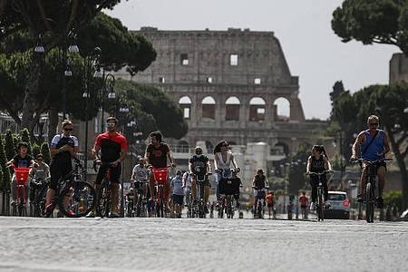 Radfahrer auf einer Straße vor dem Kolosseum in Rom. Foto: Cecilia Fabiano/LaPresse/AP/dpa