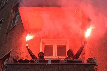 Zwei Personen halten während einer Demonstration linker und linksradikaler Gruppen durch Wedding zwei brennende Rauchfackeln auf einem Balkon. Foto: Christophe Gateau/dpa