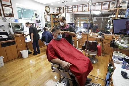 Kunden sitzen in einem New Yorker Friseurladen. Foto: Wang Ying/XinHua/dpa