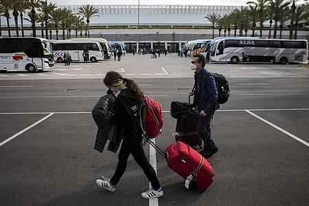 Passagiere mit Mund-Nasen-Schutz kommen am Flughafen Palma de Mallorca an. Foto: Francisco Ubilla/AP/dpa