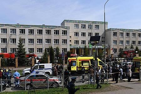 Einsatzkräfte von Polizei und Rettungsdiensten stehen vor einem Gymnasium. Bei einem Angriff auf die Schule sind mehrere Menschen getötet worden. Foto: Maksim Bogodvid/Sputnik/dpa
