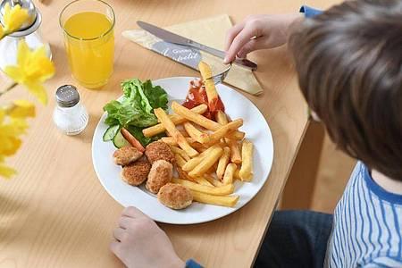 Junkfood wie Chicken Nuggets mit Pommes und Ketchup sollten Kinder nur gelegentlich essen. Foto: Tobias Hase/dpa/dpa-tmn