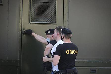 Polizeibeamte mit Mundschutzmasken halten während einer Kundgebung in Minsk einen Demonstranten fest. Foto: Str/AP/dpa