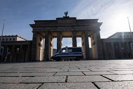 """Ein Einsatzwagen der Polizei steht am Brandenburger Tor. Rund um das Brandenburger Tor wollen am Samstag Rechtsextreme und """"Reichsbürger"""" demonstrieren. Foto: Paul Zinken/dpa-Zentralbild/dpa"""