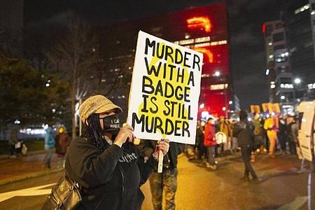 Eine Frau hält während eines Protests in Minneapolis ein Schild mit der Aufschrift «Murder with a badge is still murder» («Mord mit einer Dienstmarke ist immer noch Mord»). Foto: Henry Pan/ZUMA Wire/dpa