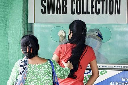 Von einer Frau im indischen Guwahati wird ein Nasenabstrich an einer Entnahmestelle genommen. Foto: David Talukdar/ZUMA Wire/dpa
